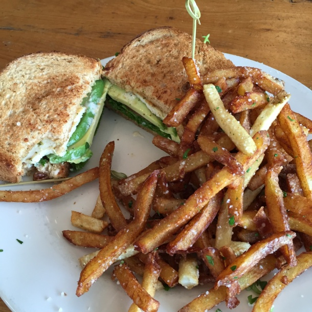 A mouthwatering chicken avocado sandwich with crisp sweet potato fries at King's Highway